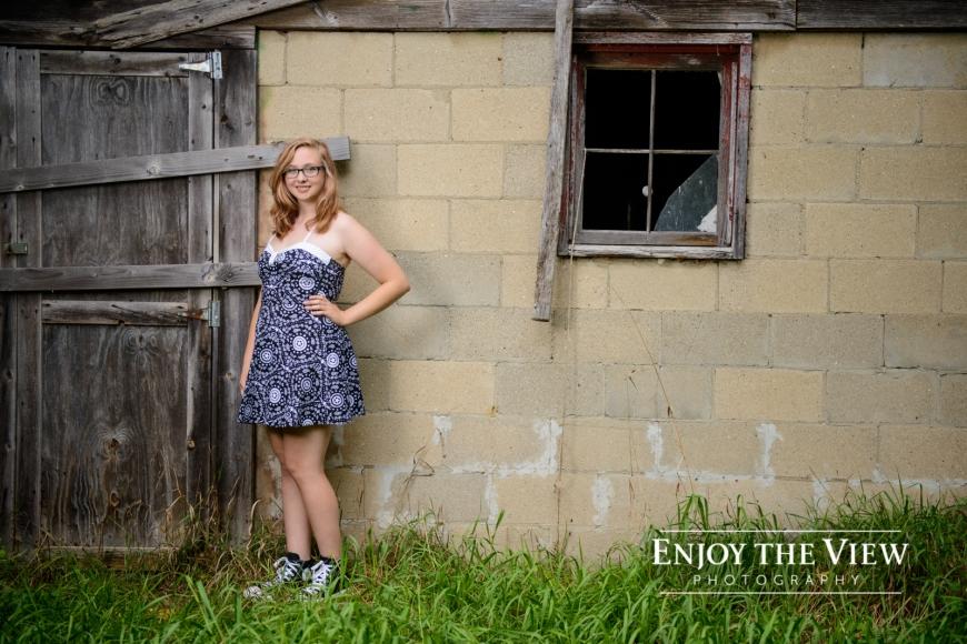 senior girl with glasses in front of door