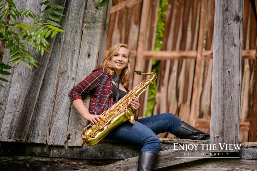 senior girl near barn with saxophone