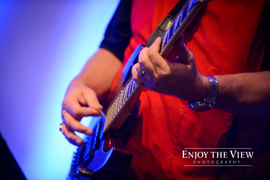 hands playing guitar in worship band
